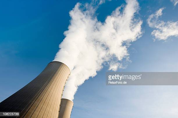 tilt shot of two steaming cooling towers with blue sky - cooling tower stock pictures, royalty-free photos & images