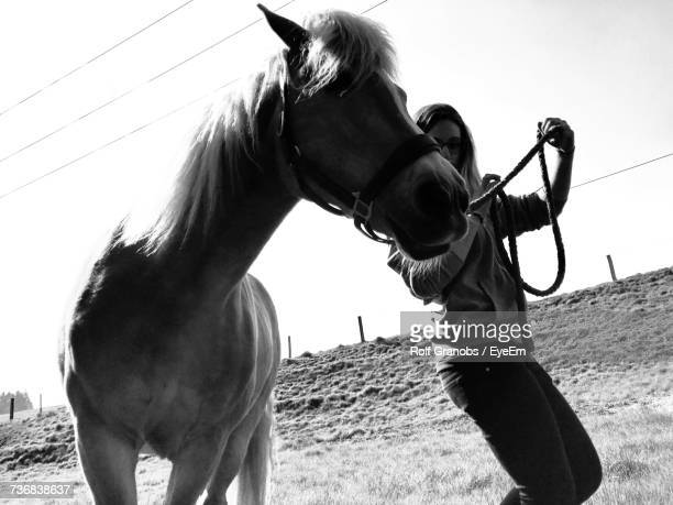 Tilt Shot Of Woman With Horse On Field Against Sky