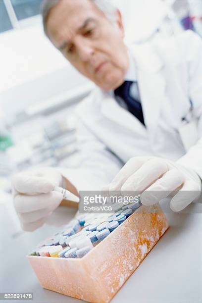 Tilted low angle view of a male scientist examining frozen test tubes