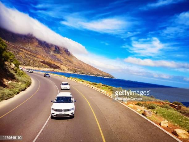 キャンプスベイ南アフリカ近くのビクトリア道路に沿って転がる車の傾斜した眺め - モバイル撮影 ストックフォトと画像