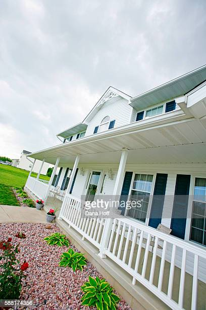 tilted view of multi-story house with porch and white siding - dana white stock pictures, royalty-free photos & images