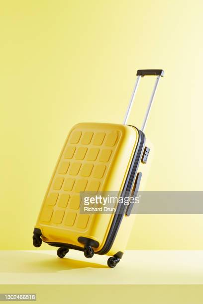 a tilted yellow suitcase on a yellow background - richard drury stock pictures, royalty-free photos & images