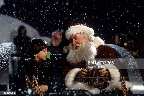 Tim Allen on a sled talking with a child in a scene from the film 'The Santa Clause', 1994.
