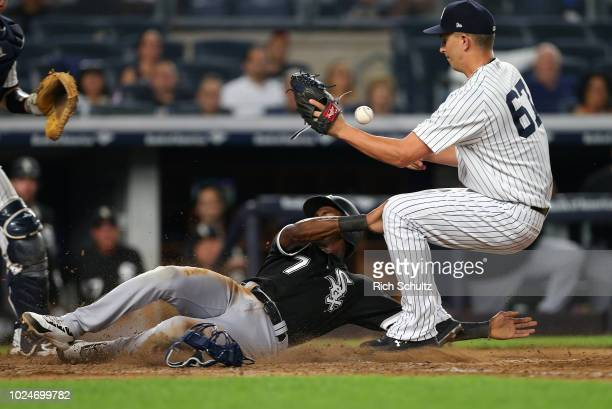 Tim Anderson of the Chicago White Sox scores on a wild pitch by AJ Cole of the New York Yankees who can't catch the ball to make a a tag at home...