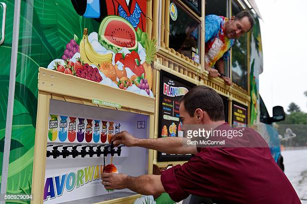 Tim Bailey pours flavored syrup on a shaved ice as David Schow looks on at the Kona Shaved Ice truck in Denver Colorado on August 24 2016 Kona serves...