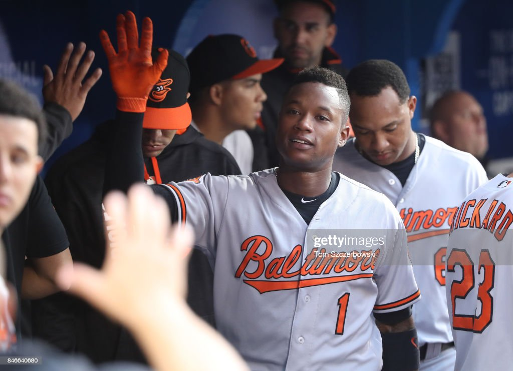 Tim Beckham #1 of the Baltimore Orioles is congratulated by teammates in the dugout after scoring a run in the first inning during MLB game action against the Toronto Blue Jays at Rogers Centre on September 13, 2017 in Toronto, Canada.