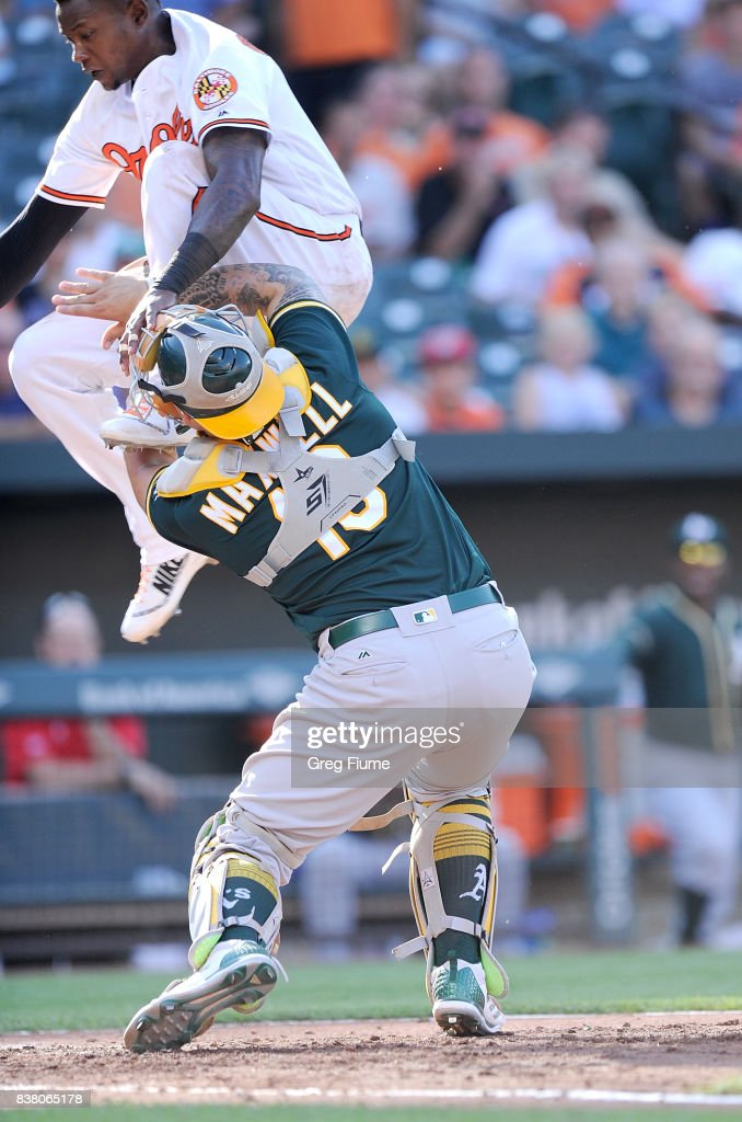 Tim Beckham #1 of the Baltimore Orioles is tagged out at home plate in the seventh inning by Bruce Maxwell #13 of the Oakland Athletics at Oriole Park at Camden Yards on August 23, 2017 in Baltimore, Maryland.