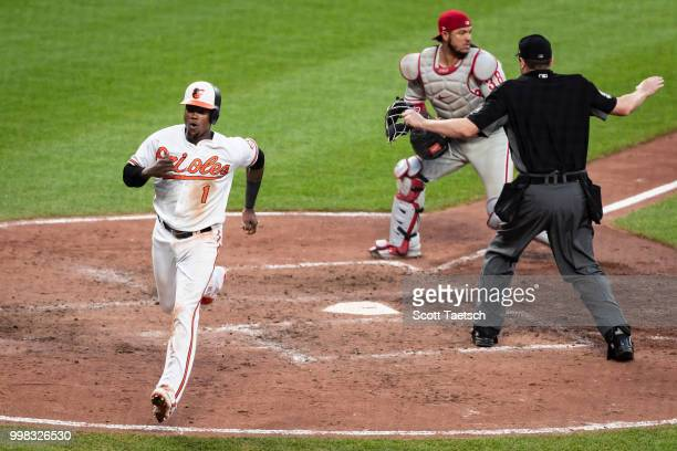 Tim Beckham of the Baltimore Orioles scores in front of Jorge Alfaro of the Philadelphia Phillies and umpire Lance Barrett during the sixth inning at...