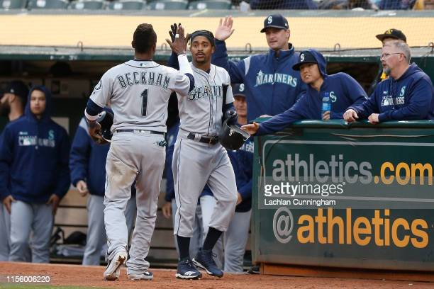 Tim Beckham of the Seattle Mariners celebrates with Mallex Smith after scoring on a sacrifice fly ball hit by Dee Gordon in the top of the fourth...