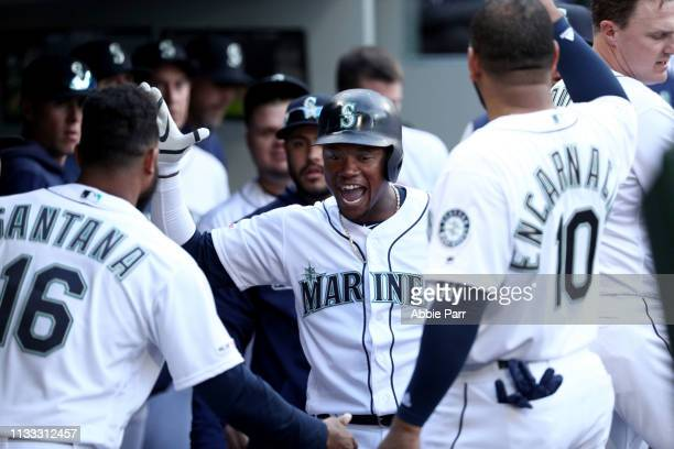 Tim Beckham of the Seattle Mariners celebrates with teammates after hitting a solo home run against the Boston Red Sox in the second inning during...