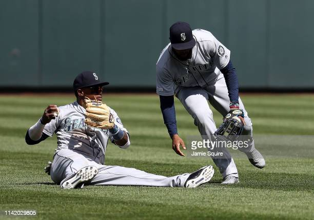 Tim Beckham of the Seattle Mariners mishandles the ball off the bat of Alex Gordon of the Kansas City Royals while Domingo Santana looks on during...