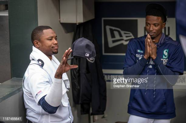 Tim Beckham of the Seattle Mariners plays around with his cap as Dee Gordon of the Seattle Mariners watches in the dugout before a game against the...