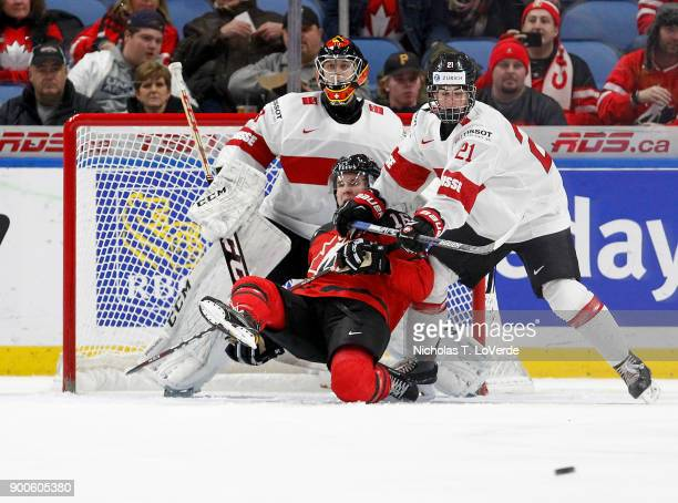 Tim Berni of Switzerland checks Taylor Raddysh of Canada to the ice in front of Philip Wüthrich of Switzerland during the second period of play in...