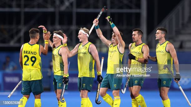 Tim Brand of Team Australia celebrates with team mates after scoring their team's seventh goal during the Men's Preliminary Pool A match between...