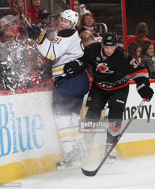 Tim Brent of the Carolina Hurricanes collides along the boards with Brayden McNabb of the Buffalo Sabres during an NHL game on January 6 2012 at RBC...