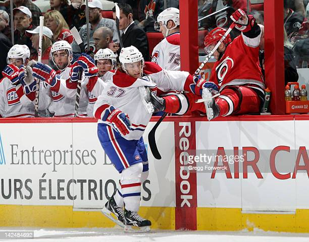 Tim Brent of the Carolina Hurricanes is checked over the boards between the benches by Gabriel Dumont of the Montreal Canadiens during an NHL game on...