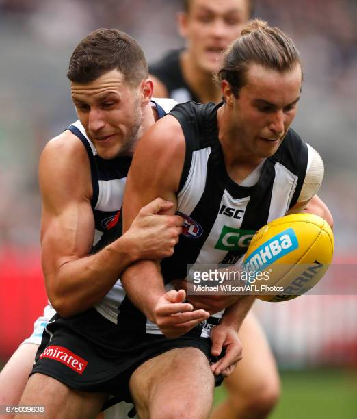 Tim Broomhead of the Magpies is tackled by Sam Menegola of the Cats during the 2017 AFL round 06 match between the Geelong Cats and the Collingwood...