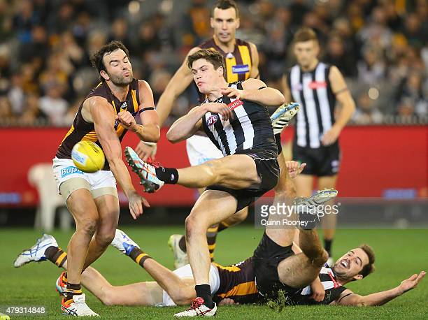 Tim Broomhead of the Magpies kicks whilst Jordan Lewis of the Hawks smouthers during the round 14 AFL match between the Collingwood Magpies and the...