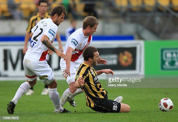 Tim Brown of the Phoenix is tackled by Nicholas Kalmar and Gerald Sibon of the Heart during the round 10 A-League match between the Wellington...