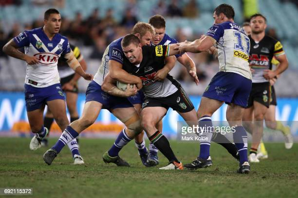 Tim Browne of the Panthers is tackled by Aiden Tolman and Josh Jackson of the Bulldogs during the round 13 NRL match between the Canterbury Bulldogs...
