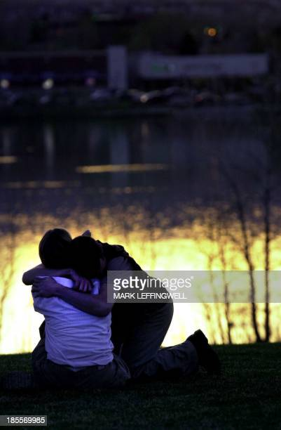 Tim Burdick kneels and hugs Kristin Van Purtfliet both Columbine students as the sun sets on the pond at Clement Park near the amphitheater in...