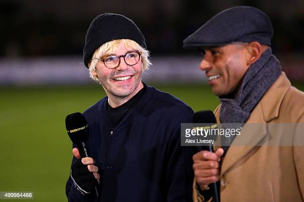 Tim Burgess Lead Singer of the Charlatans talks with former footballer Trevor Sinclair during the Emirates FA Cup Second Round match between Salford...