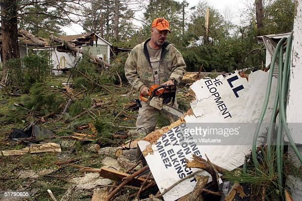Tim Burris cuts up debris that fell on a friend's home in the aftermath of tornado damage on November 24, 2004 in Olla, Louisiana. Tornados swept...