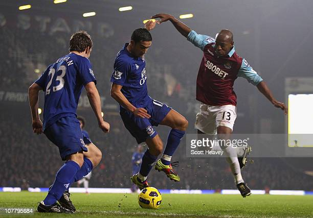 Tim Cahill and Luis Boa Morte of West Ham United battle for the ball as Seamus Coleman of Everton looks on during the Barclays Premier League match...