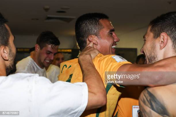 Tim Cahill hugs Aziz Behich as Australia celebrate victory in the change room after winning the 2018 FIFA World Cup Qualifiers Leg 2 match between...