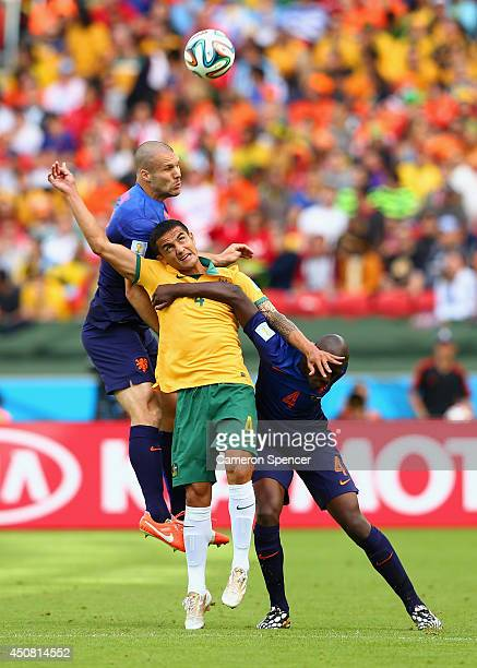 Tim Cahill of Australia competes for the ball with Ron Vlaar and Bruno Martins Indi of the Netherlands during the 2014 FIFA World Cup Brazil Group B...