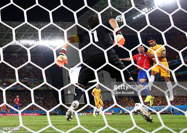 Tim Cahill of Australia goes up for a header against Gary Medel of Chile and scores a goal past goalkeeper Claudio Bravo during the 2014 FIFA World...