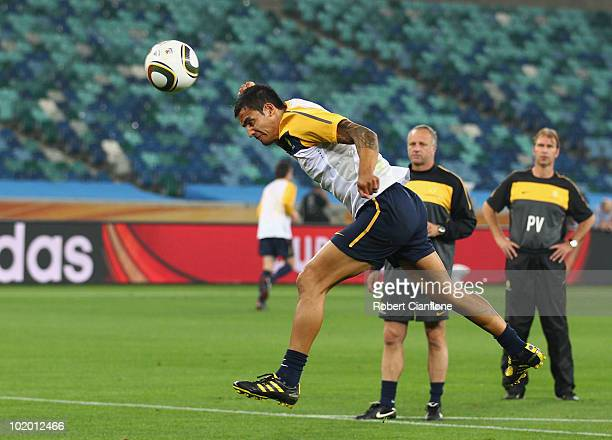 Tim Cahill of Australia heads the ball as assitant coach Graham Arnold and head coach Pim Verbeek look on during a Socceroos training session at the...