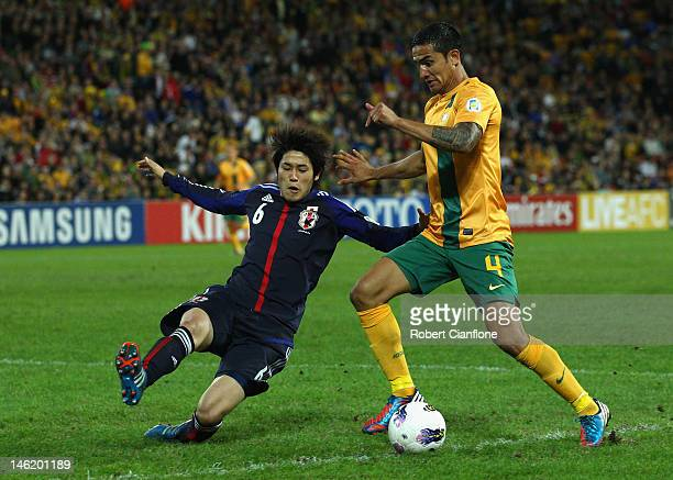 Tim Cahill of Australia is challenged by during the FIFA World Cup Asian Qualifier match between the Australian Socceroos and Japan at Suncorp...