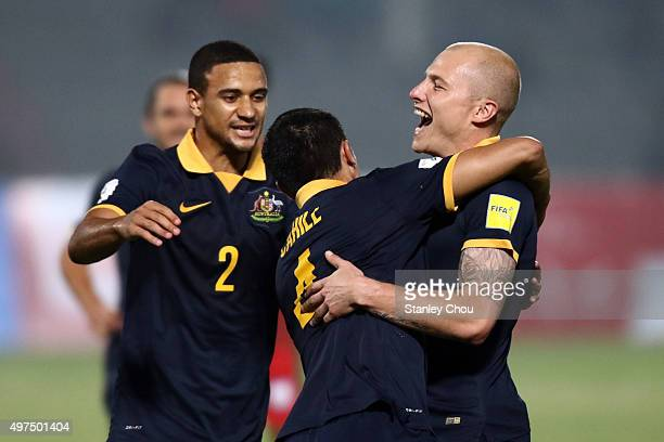 Tim Cahill of Australia Socceroos celebrates with teammates Aaron Mooy#13 and James Meredith#2 after scoring the 1st goal against Bangladesh during...