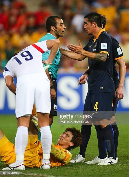 Tim Cahill of Australia throws his arms in the air as he questions referee Nawaf Shukralla whilst Kim Jin Hyeon of South Korea lies injured during...