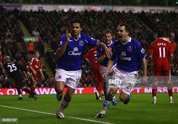 Tim Cahill of Everton celebrates scoring an equalising goal with team mate Leon Osman during the Barclays Premier League match between Liverpool and...