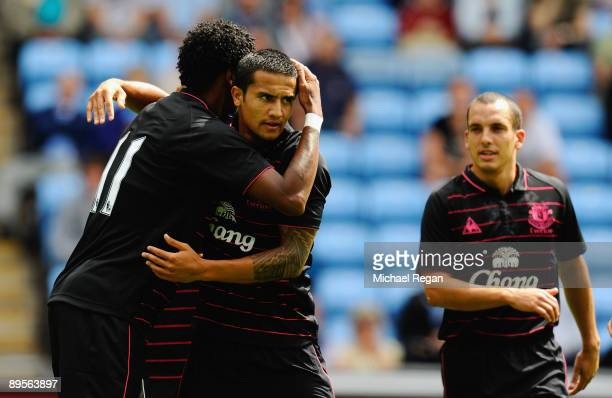 Tim Cahill of Everton is congratulated by team mate Jo and Leon Osman after scoring the opening goal during the pre season friendly match between...