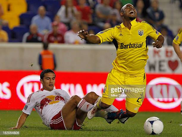 Tim Cahill of the New York Red Bulls trips up Julius James of the Columbus Crew at Red Bull Arena on September 15 2012 in Harrison New Jersey Red...