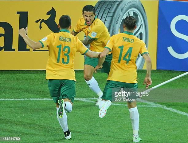 Tim Cahill of the Socceroos is congratulated by his teammates after scoring a goal during the 2015 Asian Cup match between the Australian Socceroos...