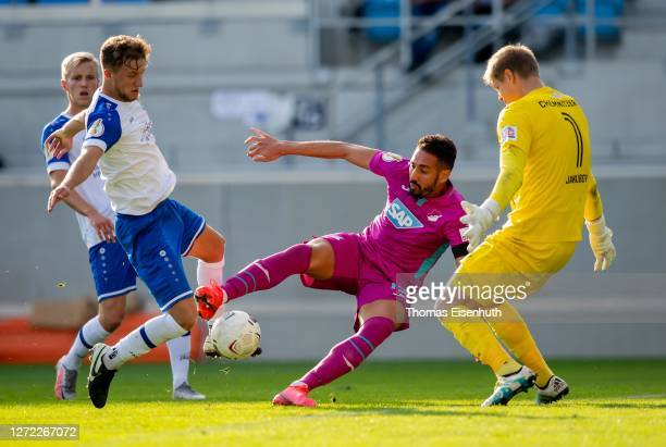 Tim Campulka and Jakub Jakubov of Chemnitzer FC are challenged by Ishak Belfodil of Hoffenheim during the DFB Cup first round match between...