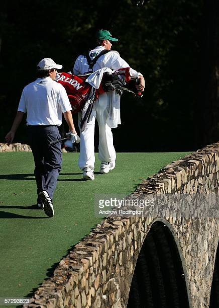 Tim Clark of South Africa and his caddie Gary Matthews walk over the Ben Hogan Bridge on the 12th hole during the final round of The Masters at the...