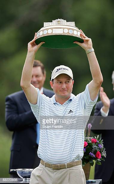 Tim Clark of South Africa is presented with the trophy for winning the final round of The Barclays Scottish Open at The Loch Lomond Golf Club on July...