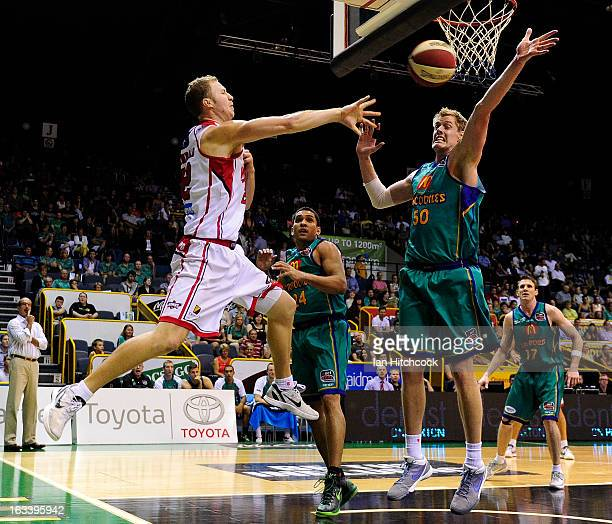 Tim Coenraad of the Hawks passes the ball past Luke Nevill of the Crocodiles during the round 22 NBL match between the Townsville Crocodiles and the...