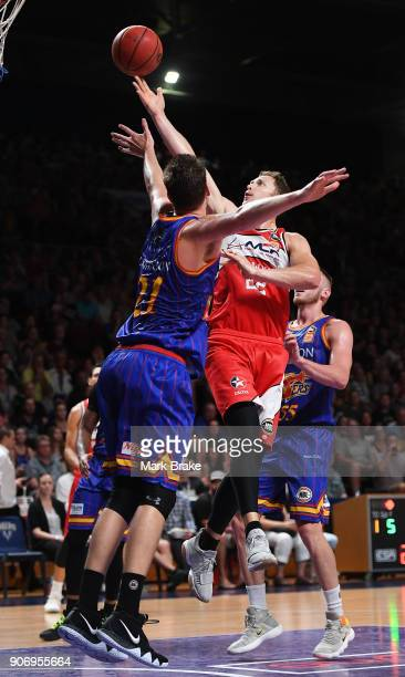 Tim Coenraad of the Illawarra Hawks layups around Daniel Johnson of the Adelaide 36ers during the round 15 NBL match between the Adelaide 36ers and...