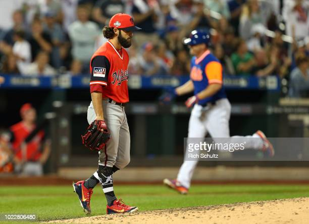 Tim Collins of the Washington Nationals walks to the back of the mound as Jay Bruce of the New York Mets rounds third base after he hit a tworun home...