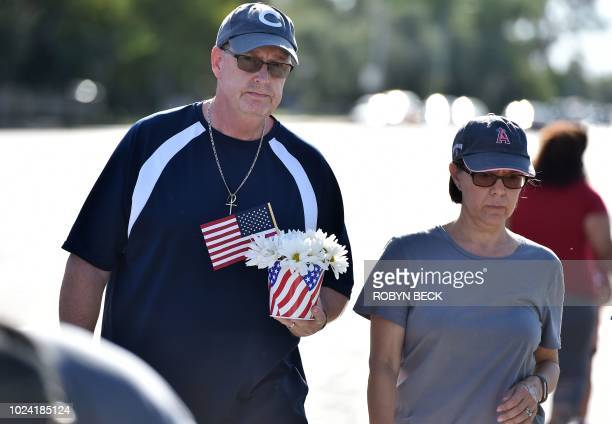 Tim Combs carries flowers to pay respect to US Senator John McCain outside a mortuary home in Phoenix Arizona August 26 2018 McCain who died on...