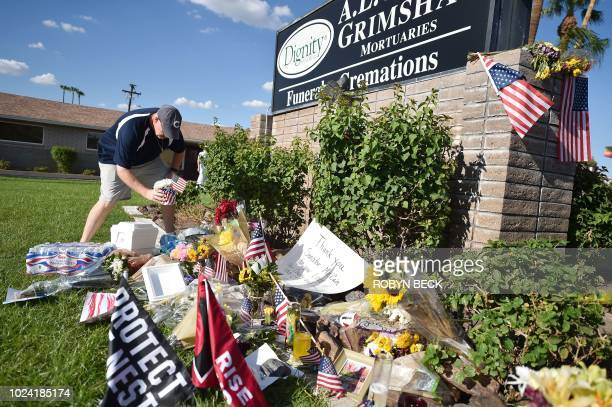 Tim Combs leaves flowers at a makeshift memorial for US Senator John McCain outside a mortuary home in Phoenix Arizona on August 26 2018 McCain who...