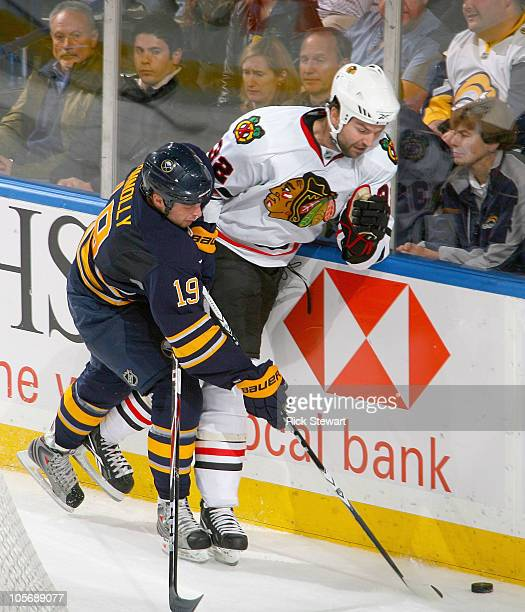 Tim Connolly of the Buffalo Sabres and John Scott of the Chicago Blackhawks fight for puck control at HSBC Arena on October 11 2010 in Buffalo New...
