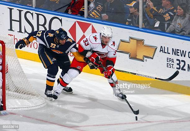 Tim Connolly of the Buffalo Sabres goes for the poke check as Bryan Rodney of the Carolina Hurricanes controls the puck during their NHL game on...
