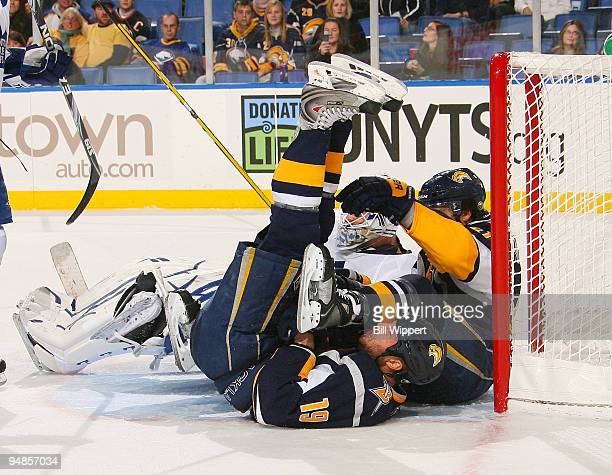 Tim Connolly of the Buffalo Sabres is upended in the goal crease getting tangled wtih teammate Clarke MacArthur and goaltender Jonas Gustavsson of...